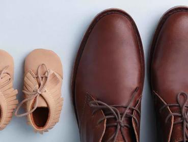 Mocassins de bébé à côté de souliers propres d'homme.